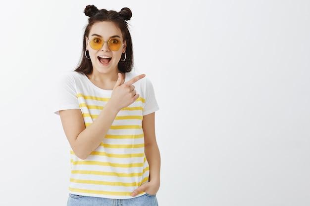 Beeindruckte junge frau, die mit sonnenbrille gegen weiße wand aufwirft