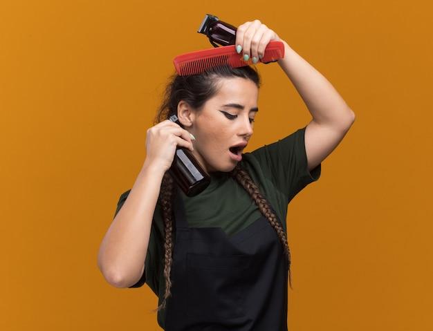 Beeindruckte junge friseurin in einheitlichen friseurwerkzeugen und kämmen der haare isoliert auf oranger wand