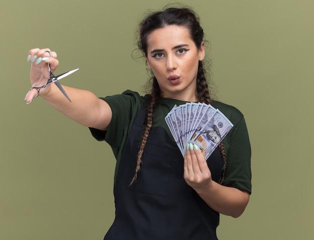 Beeindruckte junge friseurin in uniform, die bargeld mit schere lokalisiert auf olivgrüner wand hält