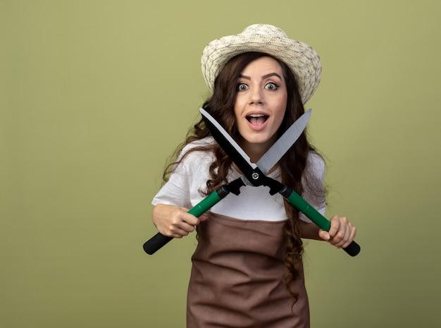 Beeindruckte junge gärtnerin in uniform mit gartenhut hält gartenschere isoliert auf olivgrüner wand