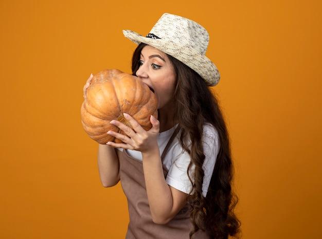 Beeindruckte junge gärtnerin in uniform mit gartenhut hält und gibt vor, kürbis zu beißen isoliert auf orange wand mit kopierraum