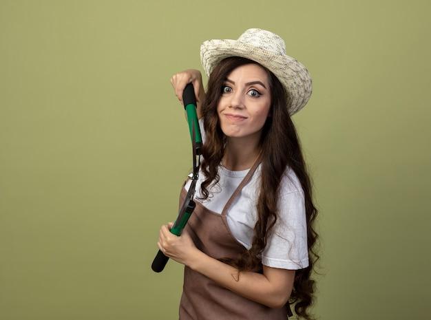 Beeindruckte junge gärtnerin in uniform mit gartenhut steht seitlich und hält gartenschere isoliert auf olivgrüner wand