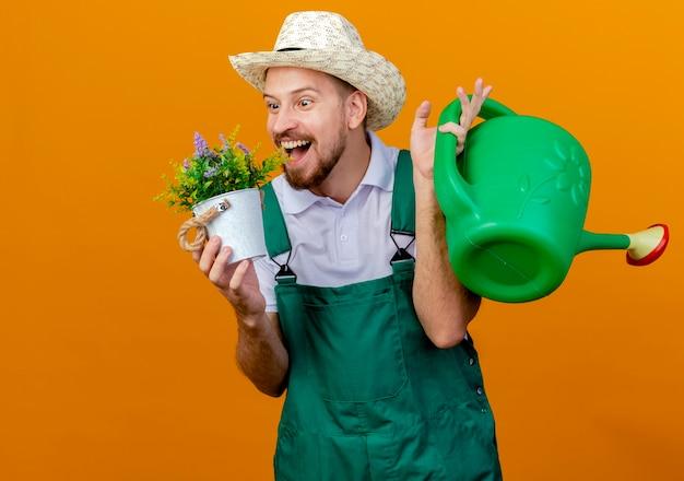 Beeindruckte junge gutaussehende slawische gärtnerin in uniform und hut, die blumentopf und bewässerungsdose betrachten blumentopf lokalisiert auf orange wand mit kopienraum