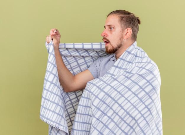 Beeindruckte junge gutaussehende slawische kranke mann eingewickelt in plaid stehend in profilansicht halten und thermometer lokalisiert auf olivgrünem hintergrund