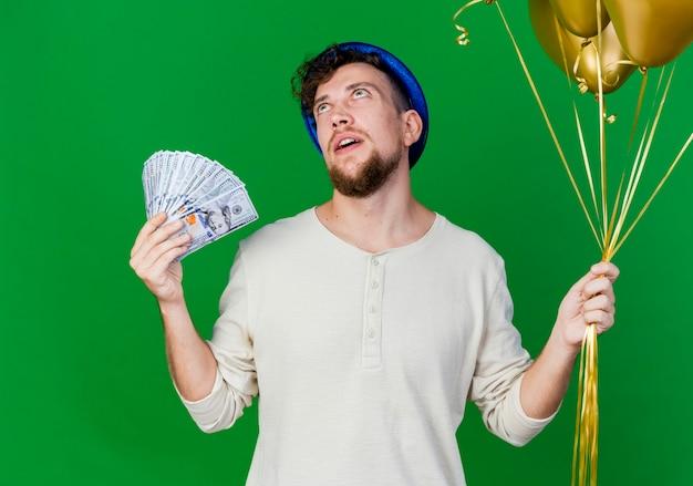 Beeindruckte junge gutaussehende slawische partei kerl, der parteihut hält, der luftballons und geld hält, die lokal auf grünem hintergrund suchen