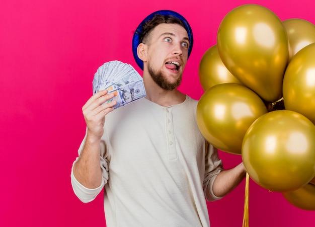 Beeindruckte junge gutaussehende slawische partei kerl, der parteihut hält, der luftballons und geld zeigt zunge zeigt seite betrachtet auf rosa wand mit kopienraum