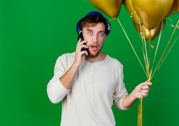 Beeindruckte junge gutaussehende slawische partei kerl, der partyhut hält, der ballone hält, die am telefon sprechen kamera betrachten, die auf grünem hintergrund mit kopienraum lokalisiert wird