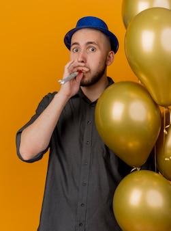 Beeindruckte junge gutaussehende slawische partei kerl, der partyhut hält, der ballons hält, die partygebläse blasen, die kamera lokalisiert auf orangefarbenem hintergrund betrachten