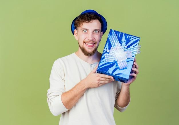 Beeindruckte junge gutaussehende slawische partei kerl tragen partyhut zeigt geschenkbox betrachten kamera lächelnd isoliert auf olivgrünem hintergrund mit kopie raum