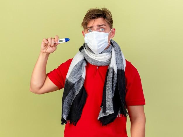 Beeindruckte junge hübsche blonde kranke mann tragen maske und schal zeigt thermometer isoliert auf olivgrüner wand