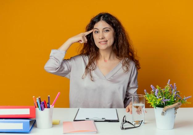 Beeindruckte junge hübsche büroangestellte, die am schreibtisch mit bürowerkzeugen sitzt, die finger auf stirn lokalisiert auf orange wand setzen