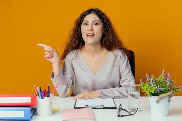 Beeindruckte junge hübsche büroangestellte, die am schreibtisch mit bürowerkzeugpunkten an der seite sitzt, lokalisiert auf orange wand mit kopienraum