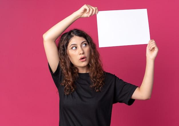 Beeindruckte junge hübsche frau, die leeres papier über dem kopf hält und es isoliert auf purpurroter wand betrachtet