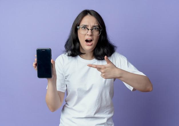 Beeindruckte junge hübsche frau mit brille, die auf handy zeigt und zeigt