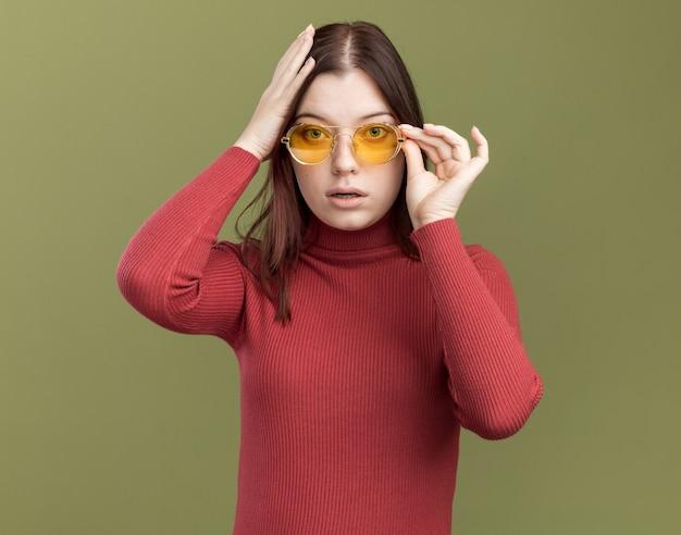 Beeindruckte junge hübsche frau mit sonnenbrille, die eine brille greift und die hand auf den kopf legt