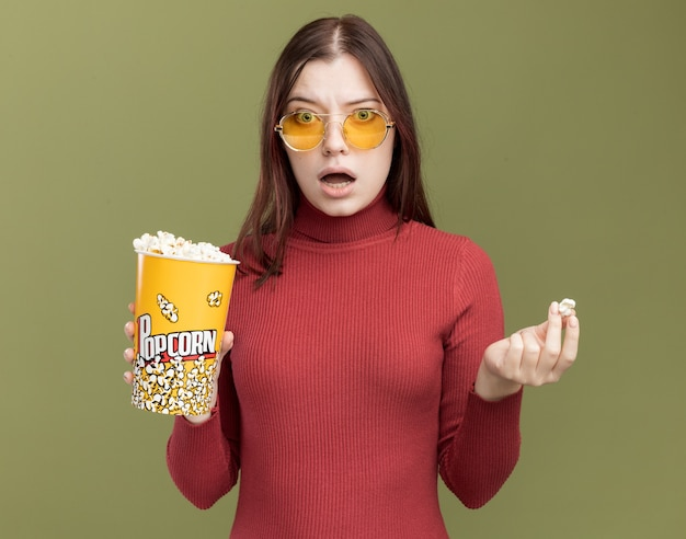 Beeindruckte junge hübsche frau mit sonnenbrille, die einen eimer mit popcorn und popcornstück hält und die vorderseite isoliert auf olivgrüner wand betrachtet
