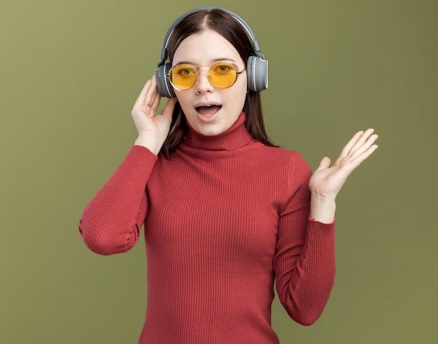 Beeindruckte junge hübsche frau mit sonnenbrille und kopfhörern, die kopfhörer berühren, die leere hand zeigen