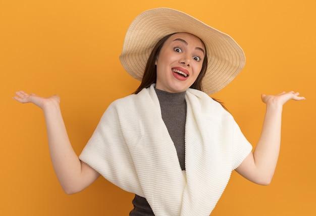 Beeindruckte junge hübsche frau mit strandhut, die leere hände zeigt