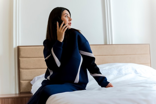 Beeindruckte junge hübsche kaukasische frau, die auf dem bett im schlafzimmer sitzt und am telefon spricht und hand auf bett legt, das seite schaut