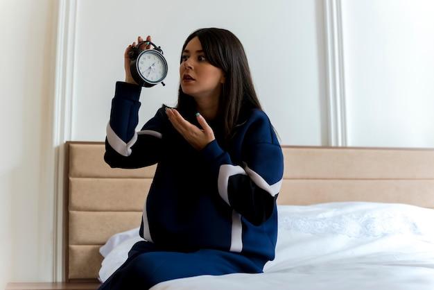Beeindruckte junge hübsche kaukasische frau, die auf dem bett im schlafzimmer sitzt und wecker hält und mit der hand darauf zeigt