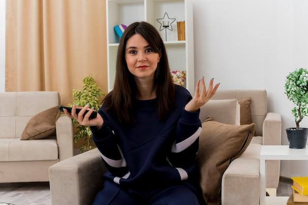 Beeindruckte junge hübsche kaukasische frau, die auf sessel im entworfenen wohnzimmer sitzt, das fernbedienung hält und hand in der luft schaut