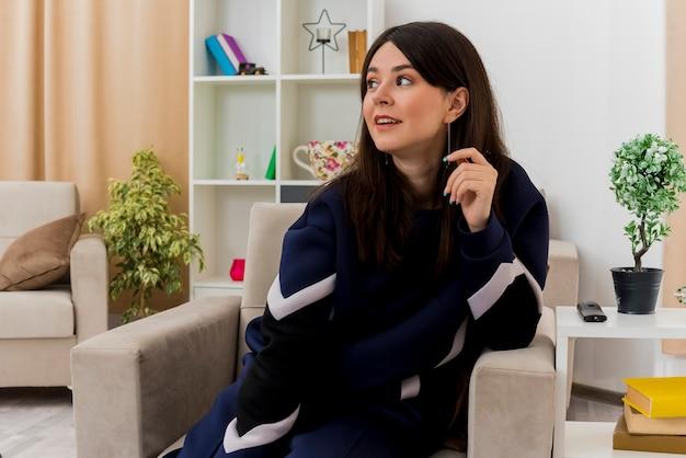 Beeindruckte junge hübsche kaukasische frau, die auf sessel im entworfenen wohnzimmer sitzt und ellbogen auf sessel setzt, der hand in der luft hält, die seite betrachtet