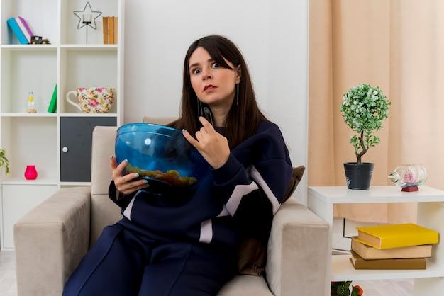 Beeindruckte junge hübsche kaukasische frau, die auf sessel in entworfenem wohnzimmer sitzt, fernbedienung und schüssel chips hält und rockgeste tut