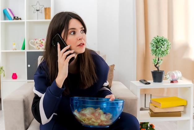 Beeindruckte junge hübsche kaukasische frau, die auf sessel in entworfenem wohnzimmer sitzt und schüssel chips hält, die seite betrachten und am telefon sprechen