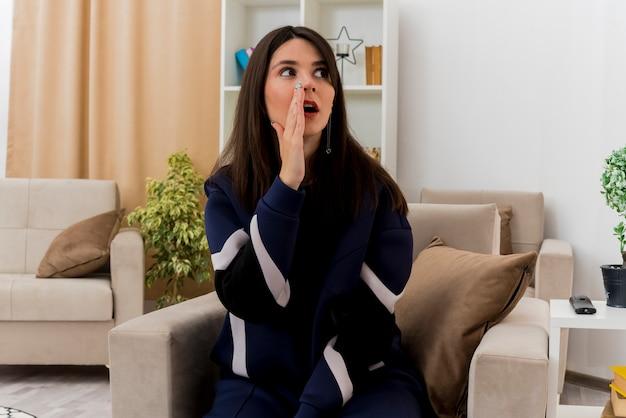 Beeindruckte junge hübsche kaukasische frau, die auf sessel in entworfenem wohnzimmer sitzt und seite betrachtet, die hand nahe mund hält, der etwas flüstert