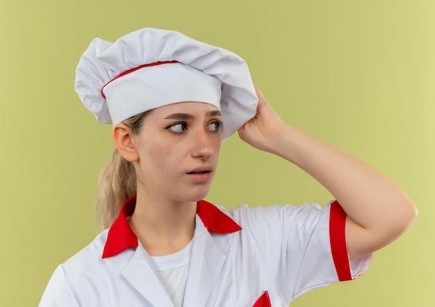 Beeindruckte junge hübsche köchin in kochuniform mit blick auf die seite, die hand auf ihren hut legt, isoliert auf grüner wand