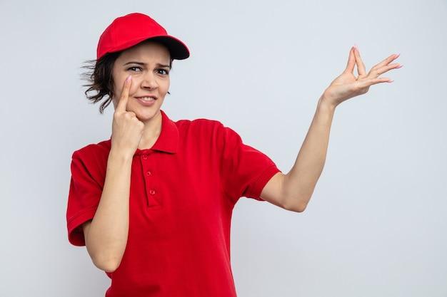 Beeindruckte junge hübsche lieferfrau, die auf ihr auge zeigt und vorgibt, etwas zu halten