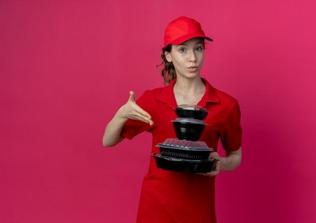 Beeindruckte junge hübsche lieferfrau, die rote uniform und kappe hält und mit der hand auf lebensmittelbehälter lokalisiert auf purpurrotem hintergrund mit kopienraum zeigt