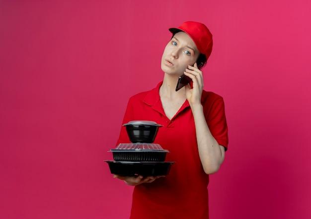 Beeindruckte junge hübsche lieferfrau, die rote uniform und kappe trägt, die am telefon spricht und lebensmittelbehälter hält, die kamera lokal auf purpurrotem hintergrund mit kopienraum betrachten