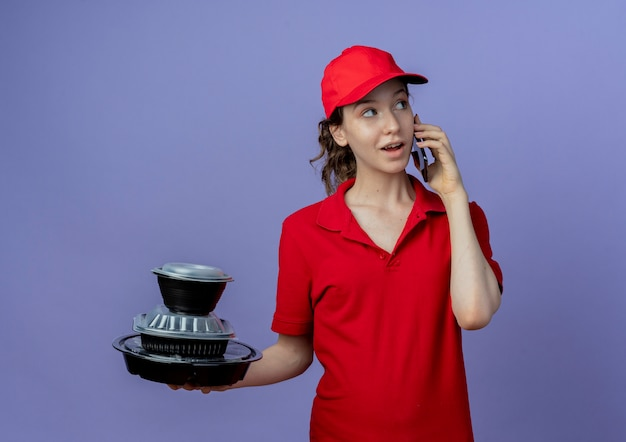 Beeindruckte junge hübsche lieferfrau, die rote uniform und mütze trägt, die seite betrachtet, die lebensmittelbehälter hält und am telefon lokalisiert auf lila hintergrund spricht