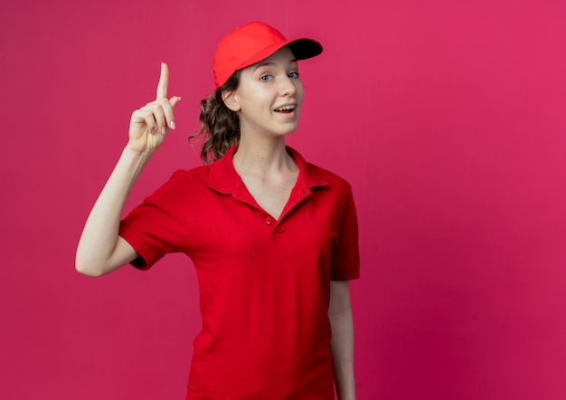 Beeindruckte junge hübsche lieferfrau in roter uniform und kappe, die finger lokalisiert auf purpurrotem hintergrund mit kopienraum anhebt