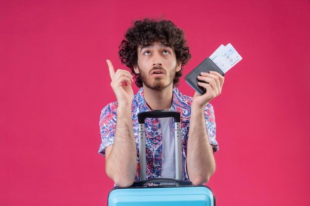 Beeindruckte junge hübsche lockige reisende mann hält brieftasche und flugtickets zeigt nach oben und legt die arme auf koffer auf isolierten rosa raum mit kopienraum
