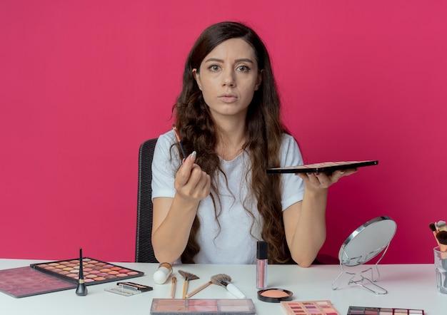 Beeindruckte junge hübsche mädchen sitzen am make-up-tisch mit make-up-tools halten lidschatten-palette und pinsel isoliert auf purpurroten hintergrund