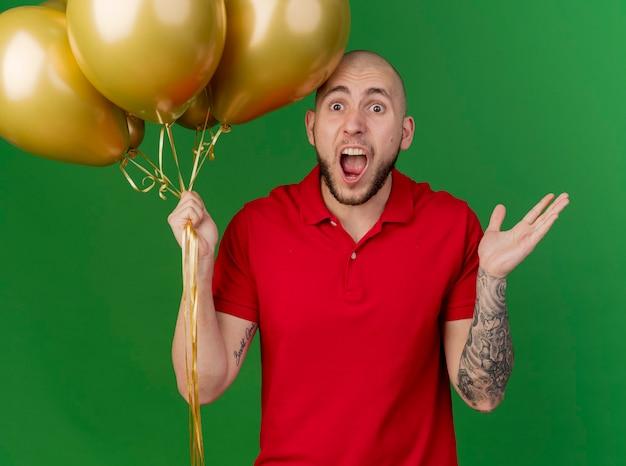 Beeindruckte junge hübsche slawische partei kerl, der ballons hält, die kamera betrachten, die leere hand lokalisiert auf grünem hintergrund zeigt