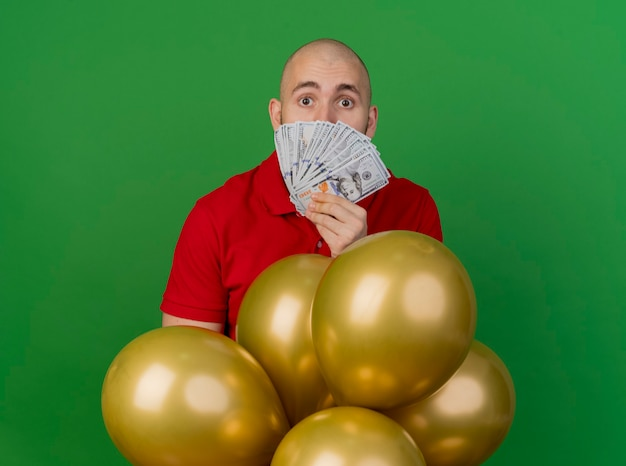 Beeindruckte junge hübsche slawische partei kerl, der hinter luftballons steht, der geld vor gesicht hält, das kamera lokalisiert auf grünem hintergrund betrachtet