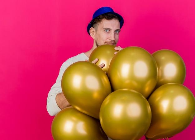 Beeindruckte junge hübsche slawische partei kerl, der parteihut trägt, der hinter luftballons steht, die einen von ihnen betrachten betrachten kamera lokalisiert auf purpurrotem hintergrund mit kopienraum