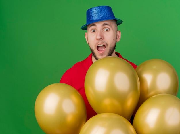 Beeindruckte junge hübsche slawische partei kerl, der parteihut trägt, der hinter luftballons steht und kamera lokalisiert auf grünem hintergrund betrachtet