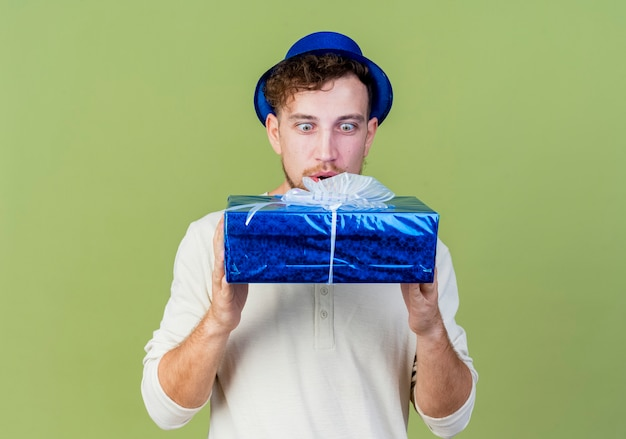 Beeindruckte junge hübsche slawische partei kerl, der partyhut hält und geschenkbox lokalisiert auf olivgrünem hintergrund mit kopienraum trägt