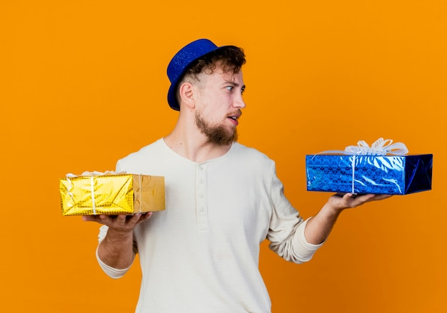 Beeindruckte junge hübsche slawische partei kerl, der partyhut hält und geschenkboxen lokalisiert auf orange hintergrund trägt