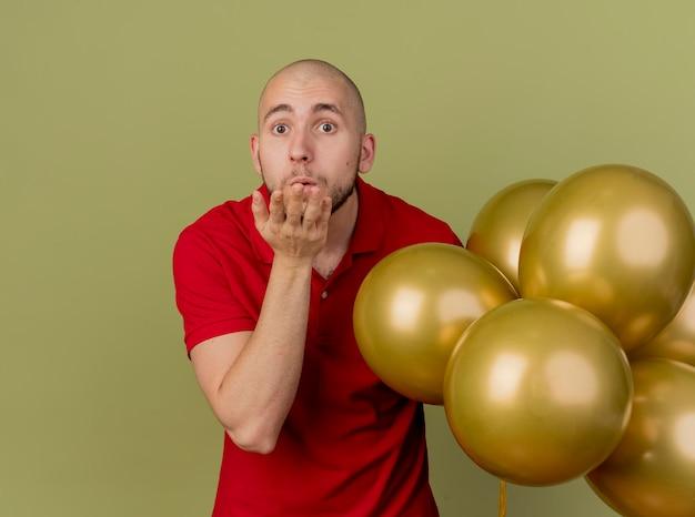 Beeindruckte junge hübsche slawische partei kerl hält luftballons, die nach vorne schauen, schlagschlagkuss lokalisiert auf olivgrüner wand mit kopienraum
