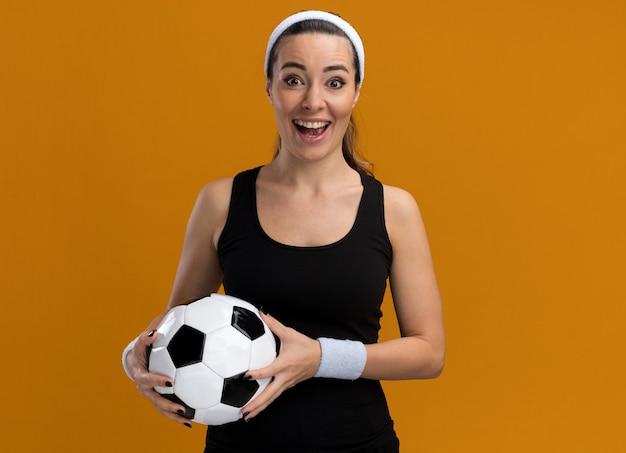 Beeindruckte junge hübsche sportliche frau mit stirnband und armbändern, die fußball hält und nach vorne isoliert auf orangefarbener wand mit kopierraum schaut
