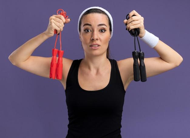 Beeindruckte junge hübsche sportliche frau mit stirnband und armbändern, die springseile in der nähe des kopfes halten