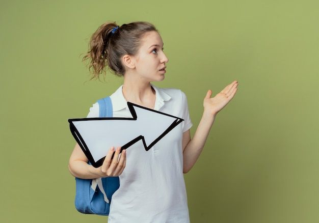 Beeindruckte junge hübsche studentin, die die rückentasche hält, die pfeilmarkierung hält, die zur seite zeigt und zur seite mit der hand zeigt, die auf hintergrund mit kopienraum lokalisiert wird