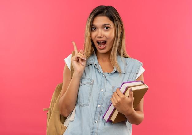 Beeindruckte junge hübsche studentin, die rückentasche hält, die bücher hält und finger lokalisiert auf rosa hebt