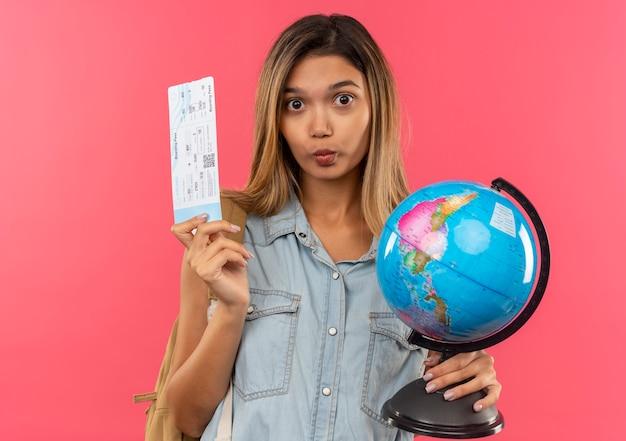 Beeindruckte junge hübsche studentin, die rückentasche hält, die flugticket und globus lokalisiert auf rosa hält
