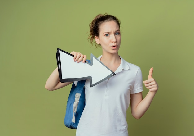 Beeindruckte junge hübsche studentin, die rückentasche hält, die pfeilmarkierung hält, die zur seite zeigt und daumen oben lokalisiert auf olivgrünem hintergrund mit kopienraum zeigt